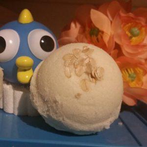 Schafmilch Sprudelkugel als Badekugel mit ein paar dekorativen Haferflocken an der Oberseite. Im Hintergrund sitzt noch ein blauer Badewannenfisch mit riesengrossen Kulleraugen zur Deko.